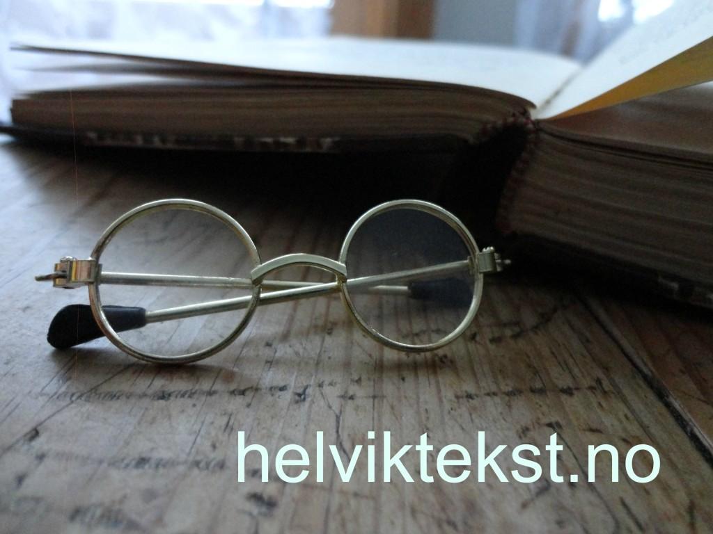 Bilete av nokre små briller i gamal stil framfor ei bok.